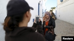 Falconer Maroua (L), for the price of a few dinars, photographs a woman as she poses with a falcon on her shoulder in Sidi Bou Said, a popular tourist destination near Tunis, Tunisia, Feb. 2, 2016.
