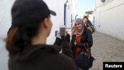 Cô Falconer Maroua (trái) chụp ảnh một người phụ nữ với chim ưng với mức giá vài dinar ở Sidi Bou Said, một địa điểm du lịch nổi tiếng gần Tunis, Tunisia, ngày 02/2/2016.
