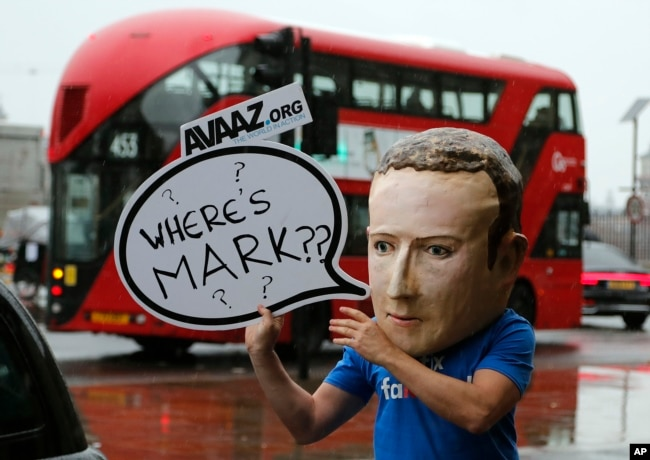 FILE - An activist wearing a Facebook CEO Mark Zuckerberg mask stands outside Portcullis House in Westminster as an international committee of parliamentarians met for a hearing on the impact of disinformation on democracy in London.