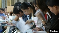 FILE - Young Filipinos fill in forms at a state-organized job fair for outsourcing firms in the Philippines outside the presidential palace in Manila, Oct. 9, 2004.