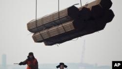 在中国唐山曹妃甸港口,工人把钢管装船。(2012年2月20日)中国钢铁产品受到欧盟制裁