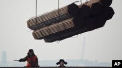 2012年2月20日,在中國唐山曹妃甸港口,工人把鋼管裝船。(資料圖片)