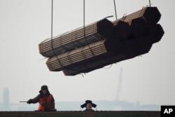 在中国唐山曹妃甸港口,工人把钢管装船。(2012年2月20日)