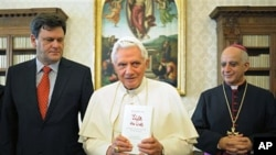 "A photo from the Vatican's Osservatore Romano shows Pope Benedict XVI, flanked by German journalist Peter Seewald (L)and by Monsignor Rino Fisichella holding a copy of the book ""Light of the World'' at the Vatican, 23 Nov 2010"