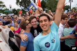 Supporters of same-sex marriage celebrate outside of the Supreme Court in Washington, Friday June 26, 2015, after the court declared that same-sex couples have a right to marry anywhere in the US.