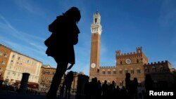 FILE - A woman walks at Del Campo square in Siena, Italy, March 12, 2012.