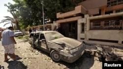 Orang-orang mengamati mobil yang rusak di luar Konsulat Swedia di Benghazi, Libya, sesudah sebuah bom mobil meledak pada 11/10/2013.
