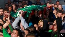 巴勒斯坦人在杰宁难民营抬着被以色列军队打死的哈马斯分子哈姆扎.阿布.海加的尸体,为他举行葬礼并呼喊抗议口号。(2014年3月22日)