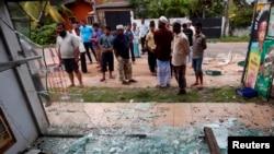 مسلمان امپارا قصبے میں ایک جلی ہوئی دکان کے پاس کھڑے ہیں۔ فائل فوٹو