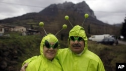 People dressed in alien costumes pose for a photo in front of Pic de Bugarach mountain at a small party in the town of Bugarach, France, Dec. 21, 2012.