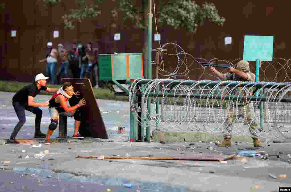 Demonstrators take cover during clashes with security forces during a protest near parliament, as Lebanon marks the one-year anniversary of the explosion in Beirut.