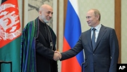 Russian President Vladimir Putin (R) and Afghan President Hamid Karzai shake hands during a meeting in Beijing, China, June 7, 2012.