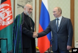 FILE - Russian President Vladimir Putin (R) and Afghan President Hamid Karzai shake hands during a meeting in Beijing, China, June 7, 2012.