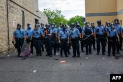 FILE - Minneapolis police officers stand in a line facing protesters demonstrating against the death of George Floyd, outside the 3rd Police Precinct in Minneapolis, Minnesota, May 27, 2020.