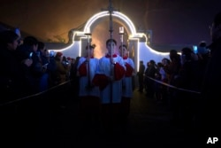FILE - Cross-bearers process through the church grounds during a Christmas Eve mass at the Southern Cathedral, an officially-sanctioned Catholic church in Beijing, Dec. 24, 2015.