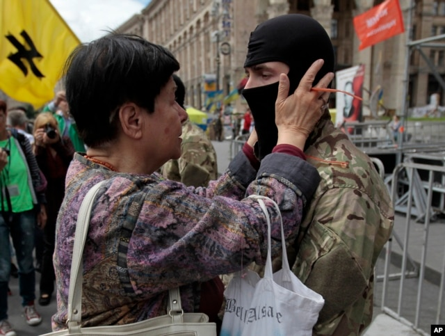 "A woman speaks with a volunteer before he sets off for eastern Ukraine to join the ranks of the special battalion ""Azov"" during a rally in Independence Square in Kiev, Ukraine, June 15, 2014."