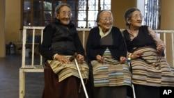 流亡藏人婦女在達蘭薩拉一家寺廟祈福後在長椅上休息