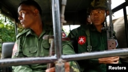 FILE - Soldiers keep watch as they sit in a vehicle outside of Thandwe in Rakhine state, Oct. 3, 2013.