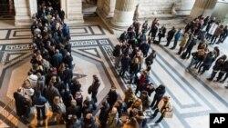 Warga berbaris saat polisi memeriksa setiap orang yang memasuki gedung kehakiman di Brussels, Belgia (16/1). (AP/Geert Vanden Wijngaert)