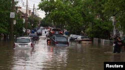 FILE - Cars are towed on a flooded street in Montreal, Quebec, May 29, 2012. Heavy rains early this week have flooded towns in several areas across the predominately French-language province.