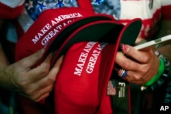 FILE - In this June 2, 2016, file photo, a woman holds hats to get them autographed by Republican presidential candidate Donald Trump during a rally in San Jose, Calif. (AP Photo/Jae C. Hong, File)