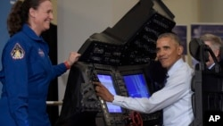 President Barack Obama sits in a flight simulator during a tour of innovation projects at the White House Frontiers Conference at University of Pittsburgh in Pittsburgh, Oct. 13, 2016, as NASA astronaut Dr. Serena Aunon-Chancellor watches.