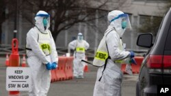Medical personnel screen people arriving at a special COVID-19 testing site in Boston, Saturday, March 28, 2020. (AP Photo/Michael Dwyer)