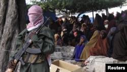 Một thành viên al-Shabab đứng gác tại một vụ đánh người phạm luật bằng roi, trước công chúng của phe Hồi giáo cứng rắn ở thành phố Bula Marer, Somalia