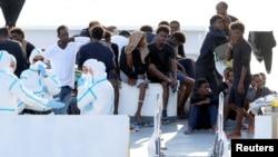"FILE - Migrants wait to disembark from the Italian coast guard vessel ""Diciotti"" at the port of Catania, Italy, Aug. 22, 2018."