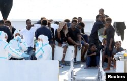 FILE - Migrants wait to disembark from the Italian coast guard vessel Diciotti at the port of Catania, Italy, Aug. 22, 2018.