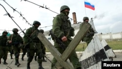 Military personnel, believed to be Russian servicemen, march outside the territory of a Ukrainian military unit in the village of Perevalnoye outside Simferopol, March 4, 2014.