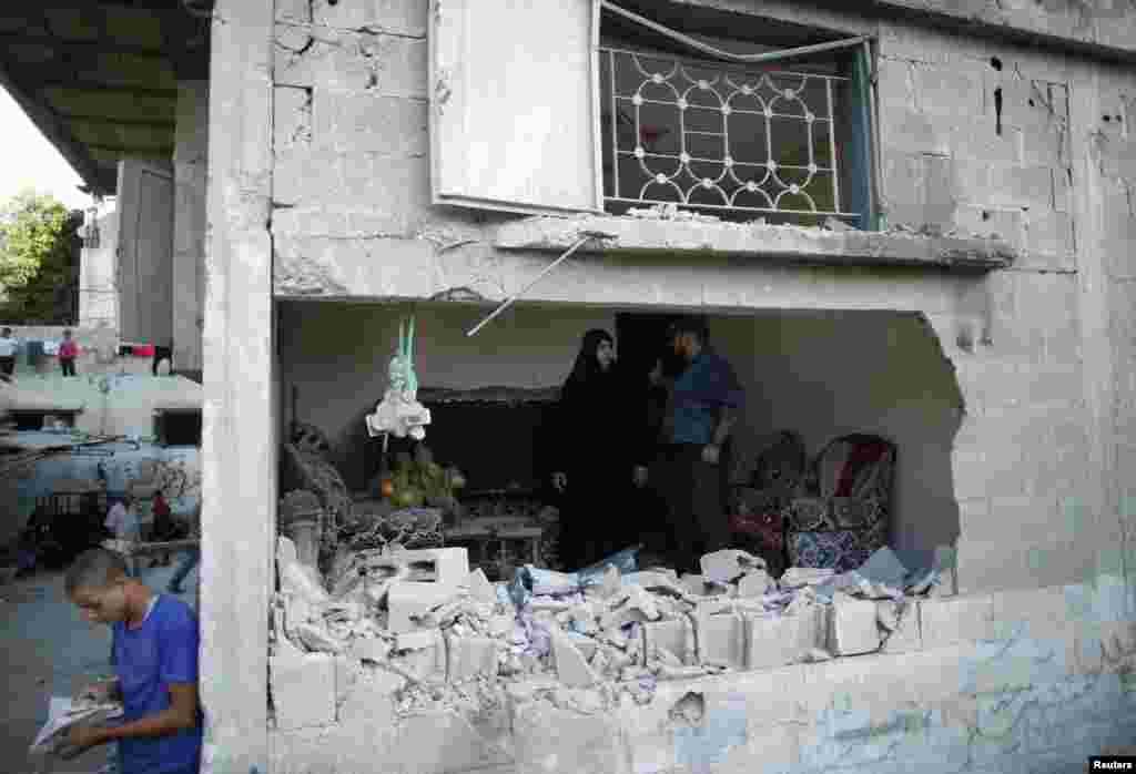 Palestinians stand inside a house which witnesses said was damaged by an Israeli air strike in Jabaliya refugee camp in the northern Gaza Strip, August 4, 2014.