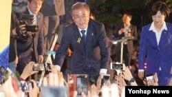 문재인 한국 대통령 당선인이 9일 서울 세종로공원에서 진행된 '시민들과 함께하는 개표방송'에서 지지자들의 손을 잡고 있다.