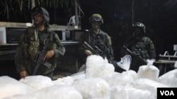 Oficiales de la policía antinarcóticos resguardan la droga decomisada en Guaracú, Puerto Gaitán.