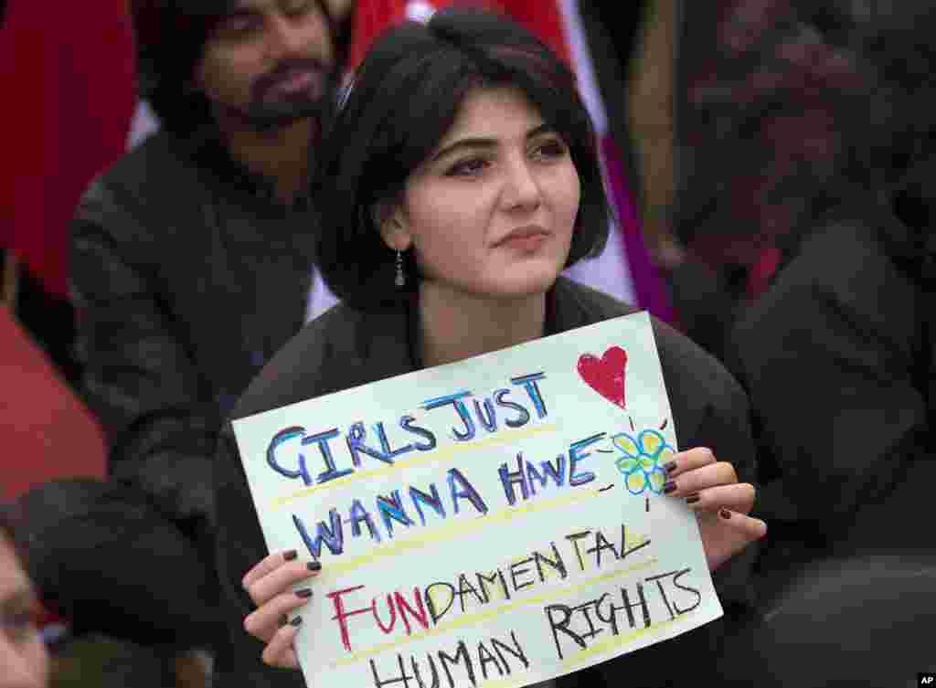 """一名巴基斯坦妇女手持""""女孩们只想拥有基本人权""""海报参加在伊斯兰堡举行的国际妇女节集会活动(2019年3月8日)。"""