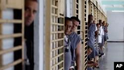 哈瓦那监狱里的囚犯在媒体参观监狱时探头张望(2013年4月9日)
