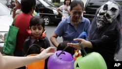 "FILE - Children wearing Halloween masks receiving candies and sweets during the ""Trick or Treat"" tradition."