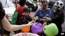 Des enfants portant des masques d'Halloween reçoivent des bonbons pendant la tradition «Trick or Treat» à Makati à Manille le 31 octobre 2008. Les parents doivent surveiller la consommation de sucre de leurs enfants selon le Dr Mary Hayes, dentiste pédiatre à Chicago. AP/Marquez
