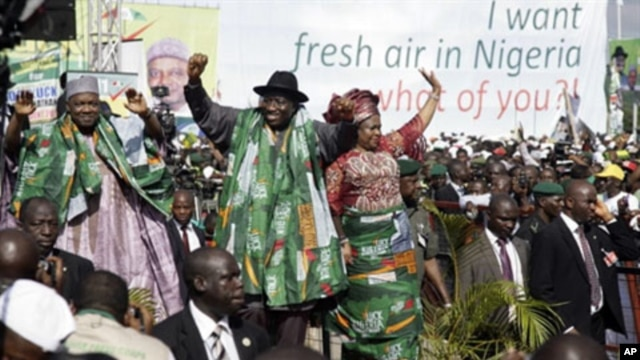 Nigeria's President Goodluck Jonathan (C) leaves a rally with his wife Patience and Vice President Namadi Sambo (L) after declaring his bid for the 2011 presidential poll in Abuja, 18 Sep 2010