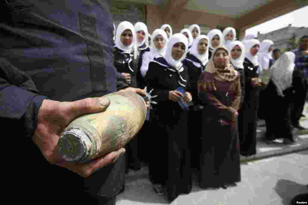 A member of Palestinian security forces loyal to Hamas carries a mortar shell as he explains to girls the dangers of unexploded ammunition, at a school in Khan Younis in the southern Gaza Strip.