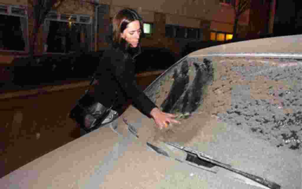 Las cenizas provenientes del volcán Puyehue, en Chile se eliminan del parabrisas de un coche por una mujer en San Carlos de Bariloche, al sur de Argentina, 4 de junio 2011. El volcán, inactivo durante décadas, estalló en el sur-centro de Chile, arrojando