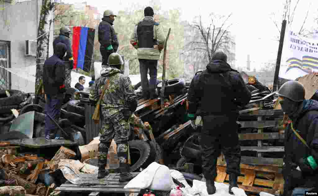 Pro-Russian men stand guard at a barricade near the police headquarters in Slovyansk, April 13, 2014.