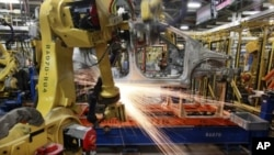 In this May 19, 2011 photo, robots weld a pre-production Chevrolet Sonic at the General Motors Orion Assembly plant in Orion Township, Michigan, USA