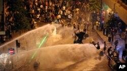 Para aktivis Lebanon menyerukan slogan-slogan anti-pemerintah di tengah semprotan air oleh polisi atas mereka di Beirut (23/8). (AP/Bilal Hussein)