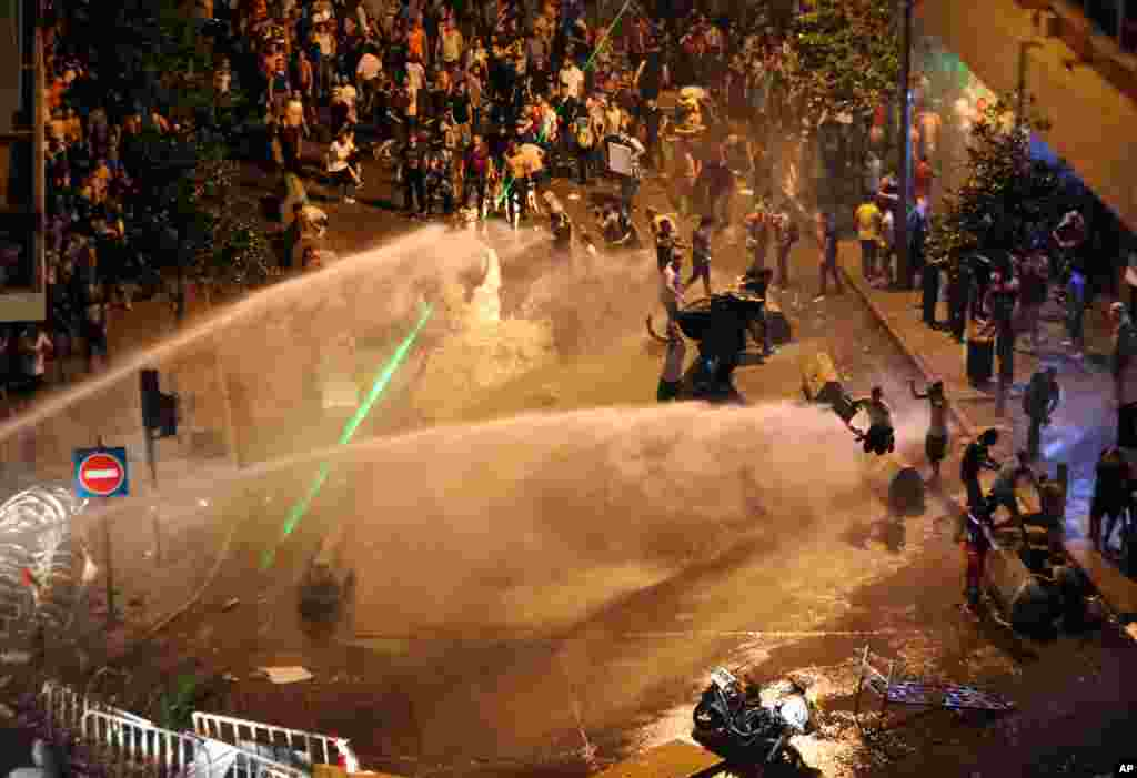 Lebanese activists shout anti-government slogans as they are sprayed by riot police using water cannons during a protest against the ongoing trash crisis, in downtown Beirut, Aug. 23, 2015.