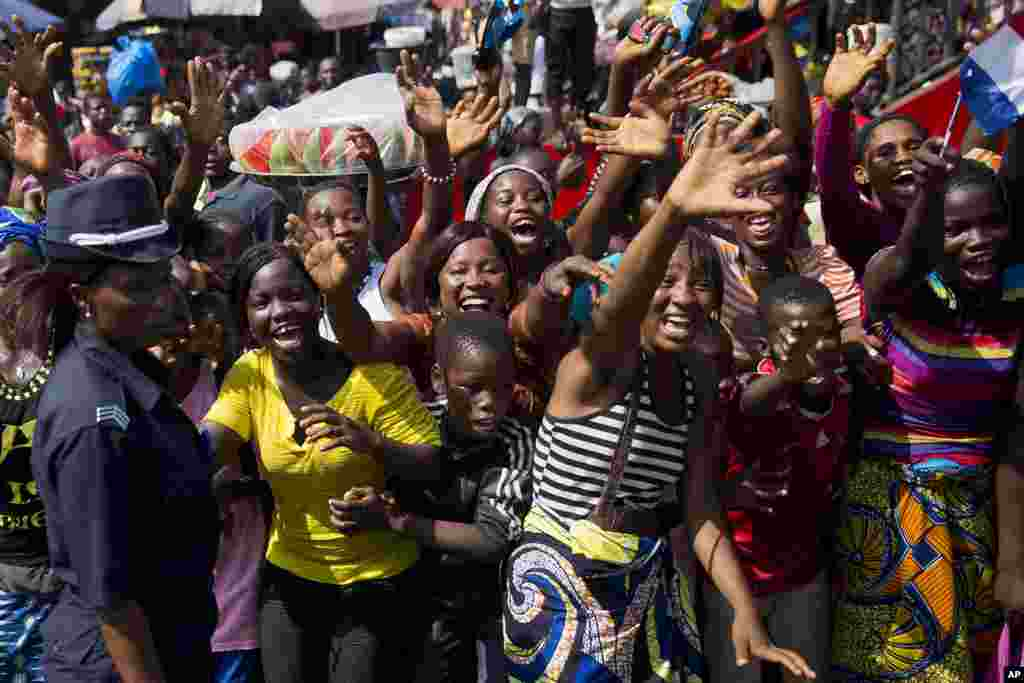 People welcome the motorcade carrying French President Francois Hollande and his Guinean counterpart Alpha Conde in Conakry, Guinea, Friday Nov. 28, 2014.