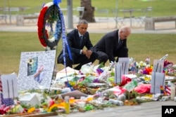 President Obama and Vice President Biden crouch in front of a memorial for Orlando victims.