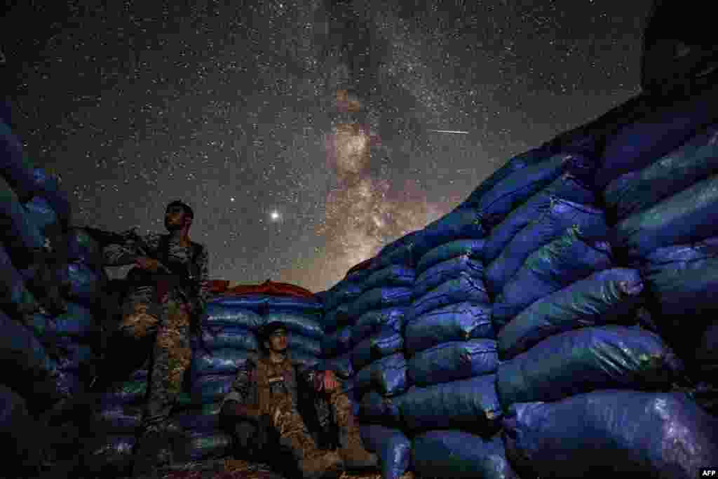 The Milky Way galaxy is seen in the sky above Syrian fighters of the Turkish-backed National Front for Liberation group while on watch duty in the town of Taftanaz along the frontlines in the rebel-held northwestern Idlib province.