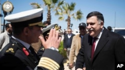 FILE - This image released by the media office of the unity government shows Fayez al-Sarraj, right, upon his arrival in Tripoli, Libya, March 30, 2016. He arrived by sea with six deputies to set up a temporary seat of power in a naval base.