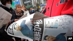 Copies of an extra edition of a Japanese newspaper reporting North Korea's nuclear test are handed out to passers-by in Tokyo Feb. 12, 2013.